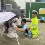 Traffic police officer guides residents to cross a flooded road with a rope during heavy rainfall in Zhengzhou